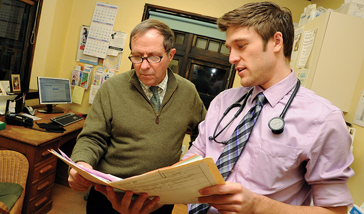 Geisel medical student Jason Laurita ('16) looks over a patient's chart with Dr. Jack Turco, one of the many physicians who volunteer at the Good Neighbor Health Clinic. Photo by Jon Gilbert Fox.