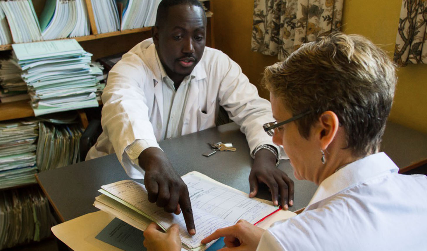 Dr. Jean-Luc Nkurikiyimfura, a Rwandan physician, works with Dr. Lisa Adams as part of the Human Resources for Health Program. Photo by Lars Blackmore.