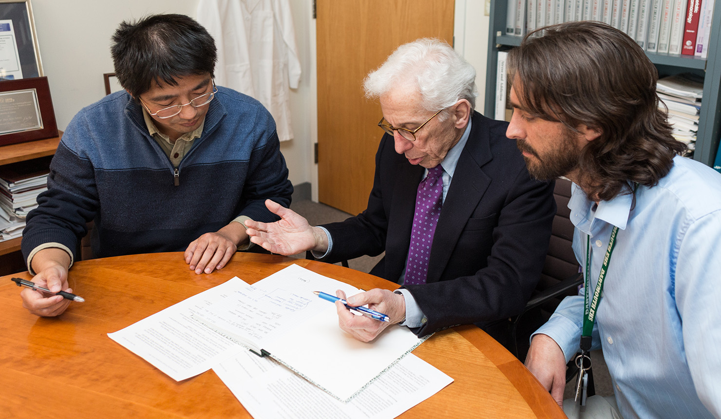Left to right, Chao Cheng, PhD, assistant professor of genetics, Alan Green, MD, director of SYNERGY, and Wilder Doucette, MD, PhD, assistant professor of psychiatry, review a research grant proposal. (Photo by Rob Strong)