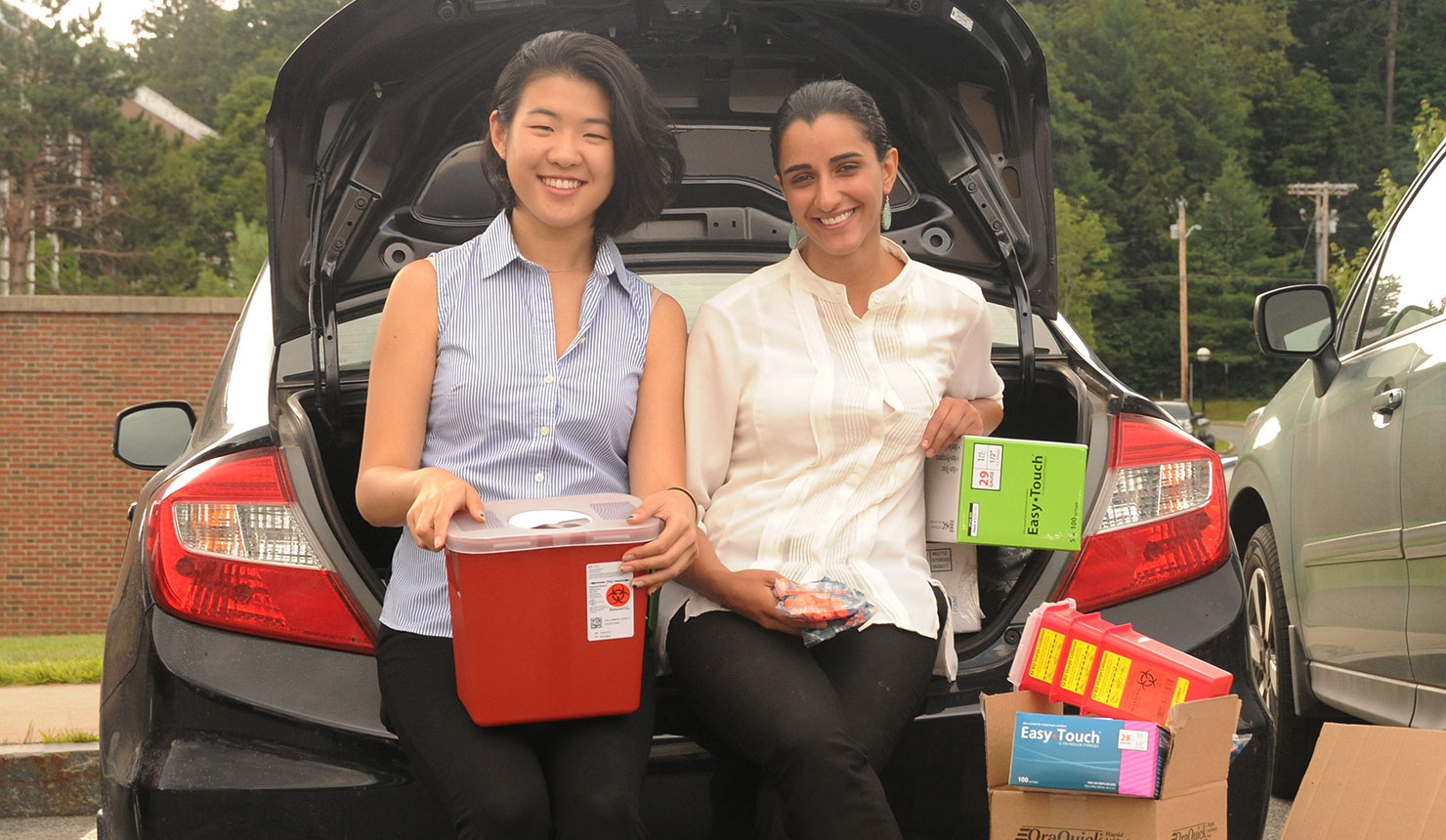 Geisel students Louisa Chen '20 (left) Nasim Azizgolshani '20 (right) load supplies for the harm reduction center they founded in Claremont, NH. (photo by Jon Gilbert Fox)